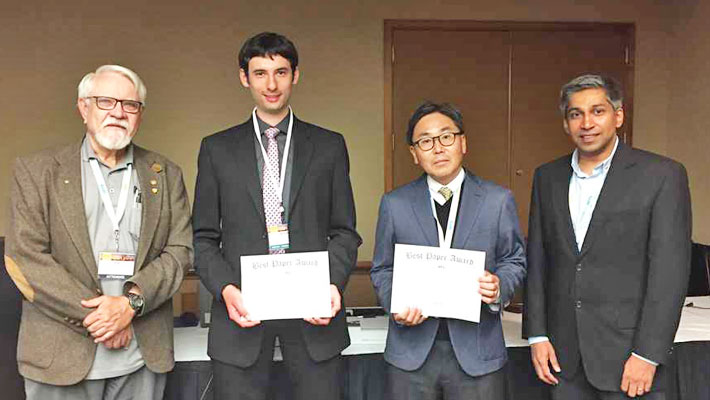 Prof. Akira Chiba (centre right) and researcher Jacob Bayless (center left) with IEEE officials.