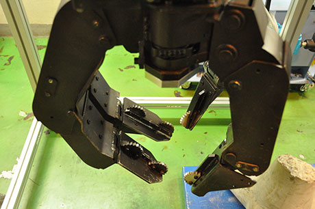 Hand robot easily lifting up a 40-kg tetrapod, an object with protrusions